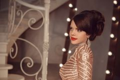 Fashionable young girl posing in golden dress at graduation prom. Party. Teen brunette with elegant hairstyle posing by modern staircase in luxury interior Royalty Free Stock Photography
