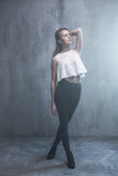 Fashionable young girl standing on a gray background textured wa Royalty Free Stock Images