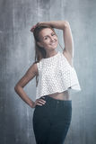 Fashionable young girl standing on a gray background textured wa Stock Photo