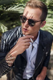 Fashionable young guy with sunglasses and leather jacket smoking cigarette. Outdoor portrait Stock Image
