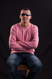 Fashionable young guy in sunglasses sitting in chair Royalty Free Stock Image