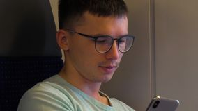 Fashionable young guy wears stylish glasses uses his phone. stock footage