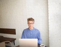 Young handsome businessman experience web content writer working on laptop computer in modern interior. Fashionable young hipster guy watching something on Royalty Free Stock Photo