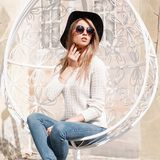 Fashionable young hipster woman in round sunglasses in a knitted vintage sweater in blue jeans in an elegant black hat sits. And rests in a hanging vintage stock photos