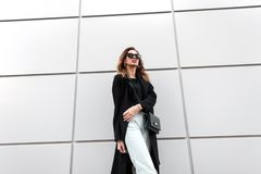 Fashionable young hipster woman in stylish clothes with a leather vintage handbag in trendy black sunglasses posing. Near a modern building in the city. Elegant royalty free stock photography