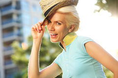 Fashionable young lady smiling with hat outside Stock Photos