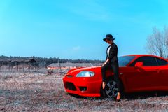Fashionable young lady in sunglasses and hat with wide brim sits on a red sport car. In the field stock image