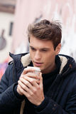 Fashionable young man drinks coffee in the street Stock Photos