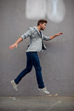 Fashionable young man jumping royalty free stock photography