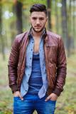 Fashionable young man. In leather jacket outdoor in a forest stock photos