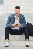 Fashionable young man with phone listening to music Royalty Free Stock Photos