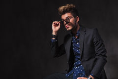 Fashionable young man posing in dark studio background while sea Royalty Free Stock Photography