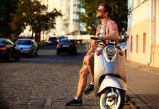 Fashionable young man riding a vintage scooter in street. Fashionable young man riding a vintage scooter in the street royalty free stock image