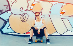 Fashionable young man sitting on a longboard in the skatepark in the summer. A skateboarder wearing white shirt, shorts and sneake Stock Photography