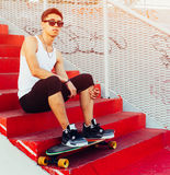 Fashionable young man sitting on red stairs. Cool guy. Wearing white shirt and black pants. resting on summer vacation. Outdoor Royalty Free Stock Photo