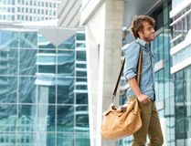 Fashionable young man smiling with travel bag Royalty Free Stock Image