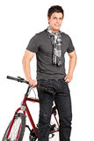 Fashionable young man standing by a bicycle Stock Photos