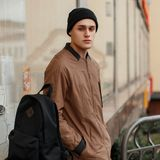 Fashionable young man in a stylish vintage coat with a hat. And a black backpack near sits on the street near showcases Stock Photography
