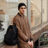 Fashionable young man in a stylish vintage coat with a hat. And a black backpack sitting near the shop window on the street Stock Images