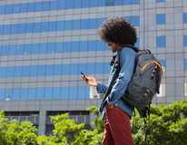 Fashionable young man walking with mobile phone. Portrait of a fashionable young man walking with mobile phone Royalty Free Stock Image