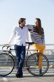Fashionable young man and woman posing with bicycle outdoors Stock Image