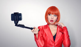 Fashionable young redhead woman in red making selfie with a stick Royalty Free Stock Photo