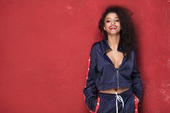 Fashionable young smiling afro girl posing. Fashionable young smiling african american girl posing on red background Stock Images