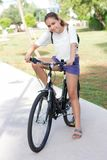 Fashionable young teen girl in shorts and t-shirt rides a bicycle in a summer park royalty free stock images