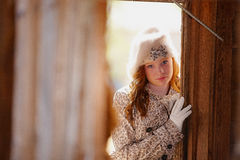 Fashionable young woman. Fashionable young girl with fur hat looking through gap in wooden home or barn Stock Photos