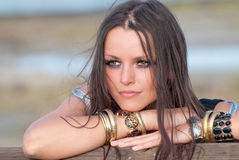 Fashionable young woman. Portrait of fashionable young woman with bangles and bracelets leaning on wooden fence Stock Images