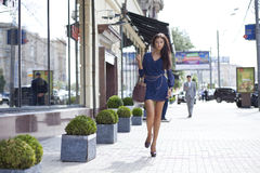 Fashionable young woman against a shop window Royalty Free Stock Photos