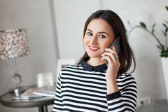 Fashionable young woman with beautiful make up talking on her cell phone amd smile on camera. Royalty Free Stock Image
