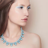 Fashionable young woman. With beautiful makeup in shades of blue and expensive necklace on her neck Royalty Free Stock Photos