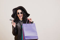 Fashionable young woman in black hat with credit card and colored shopping bags over white studio background. royalty free stock images