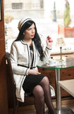 Fashionable young woman in black and white outfit drinking coffee in restaurant. Royalty Free Stock Photo