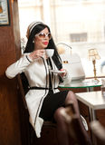 Fashionable young woman in black and white outfit drinking coffee in restaurant. Beautiful brunette in elegant scenery Stock Photo