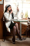 Fashionable young woman in black and white outfit putting lipstick on her lips and drinking coffee in restaurant Royalty Free Stock Image