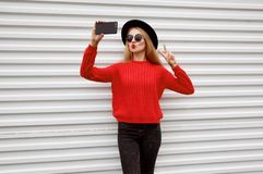 Fashionable young woman blowing red lips sends sweet air kiss taking selfie picture by phone in knitted sweater. On white wall background stock photos