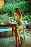 Fashionable young woman drink tea and working on laptop Royalty Free Stock Images