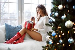 Fashionable young woman in a festive red Christmas outfit lying in her living room enjoying Christmas. royalty free stock photos