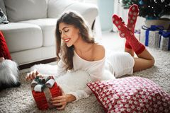 Fashionable young woman in a festive red Christmas outfit lying in her living room enjoying Christmas. stock image
