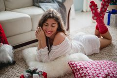 Fashionable young woman in a festive red Christmas outfit lying in her living room enjoying Christmas. stock photos