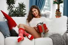 Fashionable young woman in a festive red Christmas outfit lying in her living room enjoying Christmas. stock images
