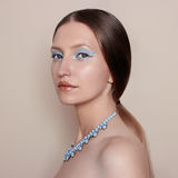 Fashionable young woman. Young girl on a beige background, with beautiful make-up in blue tones and expensive necklace on her neck Stock Photography