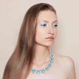 Fashionable young woman. Young girl on a beige background, with beautiful makeup in blue tones and expensive necklace on her neck Royalty Free Stock Images