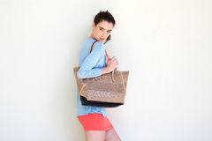 Fashionable young woman holding purse against white wall Stock Photos