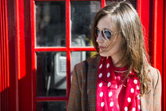 Fashionable young woman leaning on red phone booth Stock Photography