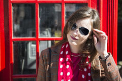 Fashionable young woman leaning on red phone booth. Portrait of beautiful young woman wearing sun glasses and leaning against London red phone booth Stock Photography