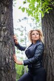 Fashionable young woman in leather jacket outdoors. Royalty Free Stock Images