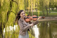 Fashionable young woman emotionally playing the violin in the park royalty free stock photo